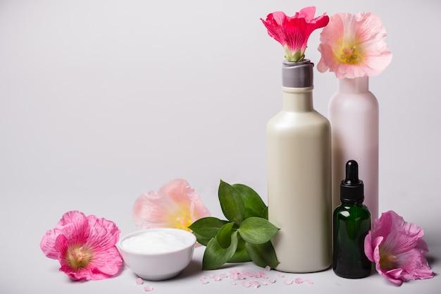 Ensemble de cosmétiques naturels et fleurs sur fond gris. concept d'écologie naturelle.