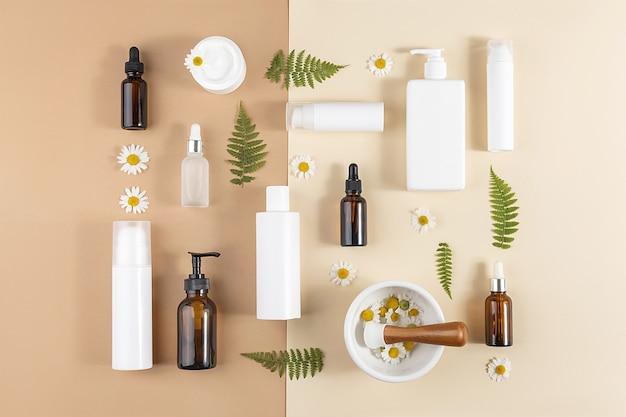 Ensemble de cosmétiques de soins. diverses bouteilles, tubes à cosmétiques, fleurs de camomille, feuilles de fougère et bol de mortier avec pilon sur fond beige et marron. notion de beauté. vue de dessus mise à plat.