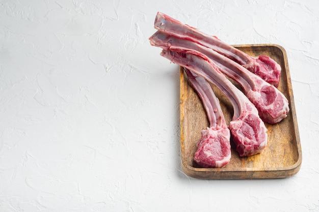Ensemble de côtelettes d'agneau gras crus français, sur table en pierre blanche
