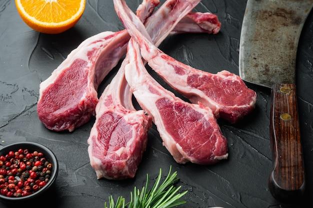 Ensemble de côtelettes de longe d'agneau frais crus, avec des ingrédients orange carotte, herbes, sur table en pierre noire