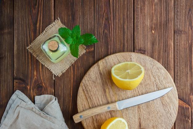 Ensemble de couteau en bois et moitié de citron dans un panier sur une surface en bois. vue de dessus. espace pour le texte
