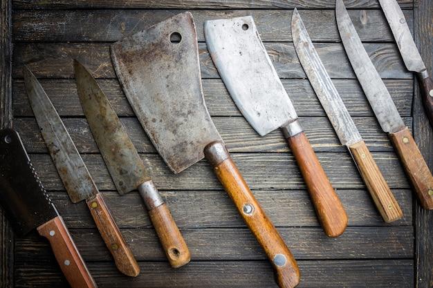 Ensemble de couteaux de cuisine vintage et couperet à viande sur bois foncé.