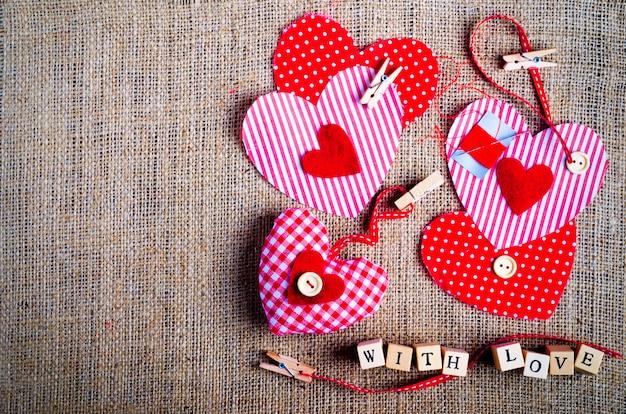 Ensemble de couture: tissus, fils, épingles, boutons, ruban adhésif et cœurs faits à la main sur toile de jute, toile de sac. tonique.