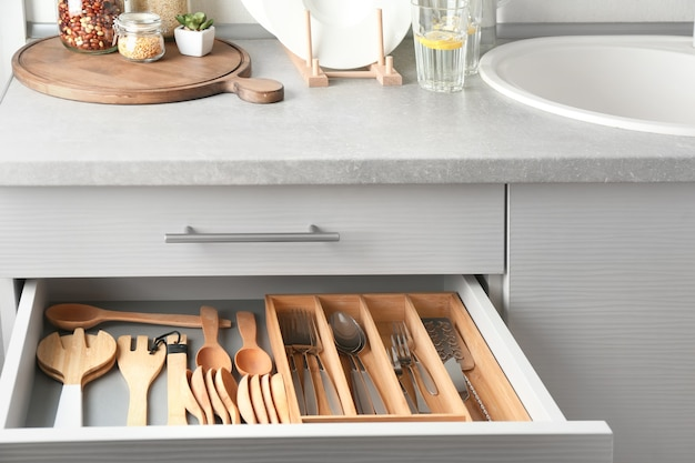 Ensemble de couverts et ustensiles en bois dans le tiroir de la cuisine