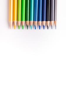 Un ensemble de crayons de couleur alignés sur la photographie verticale. sur un fond blanc.