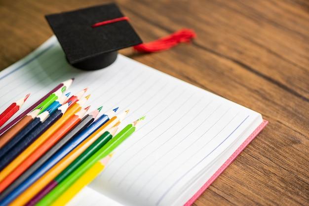 Ensemble de crayons de couleur et cap de la remise des diplômes sur un cahier en papier blanc à l'école et concept d'éducation - crayons