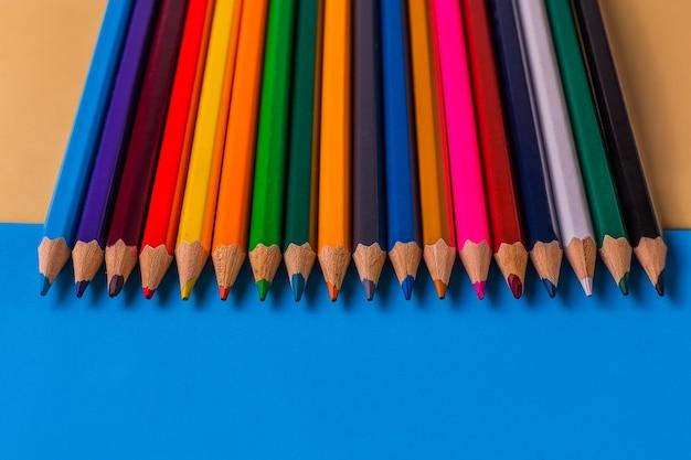 L'ensemble des crayons de couleur sur fond de papier coloré.