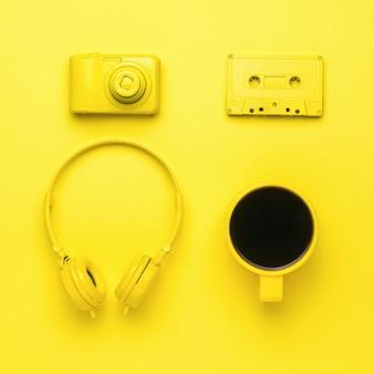 Un ensemble créatif de cafés et d'accessoires informatiques sur fond jaune. tendance de couleur.