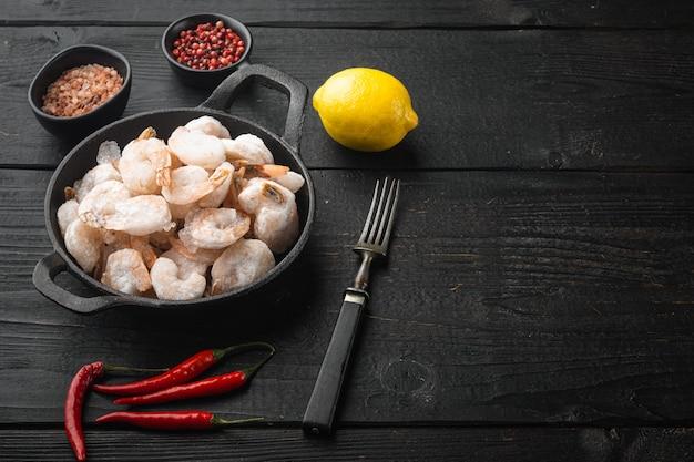 Ensemble de crevettes bouillies et congelées, dans une poêle ou une marmite en fonte, sur une table en bois noir, avec espace de copie pour le texte