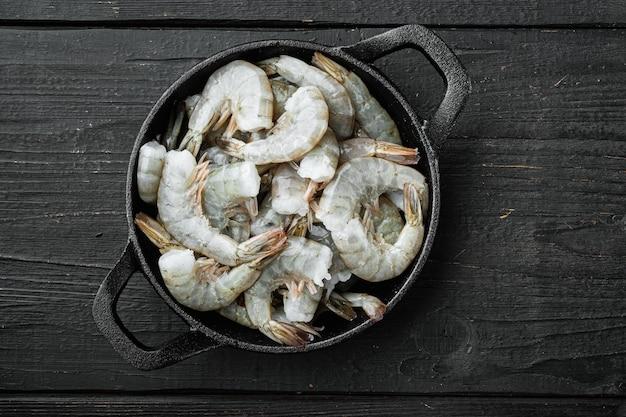 Ensemble de crevettes tigrées biologiques saines, dans une poêle à frire en fonte, sur fond de bois noir, vue de dessus à plat