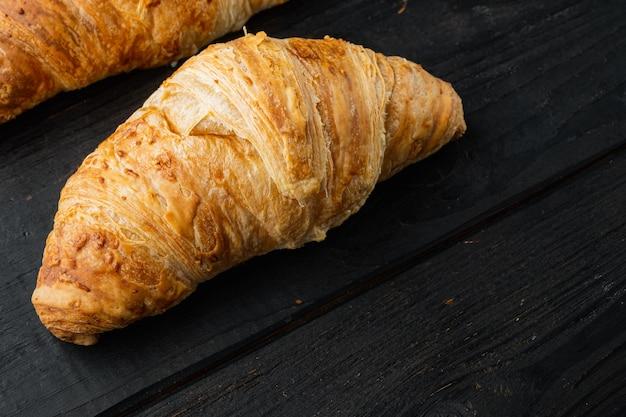 Ensemble de croissants frais croustillants, sur fond de table en bois noir, avec espace de copie pour le texte