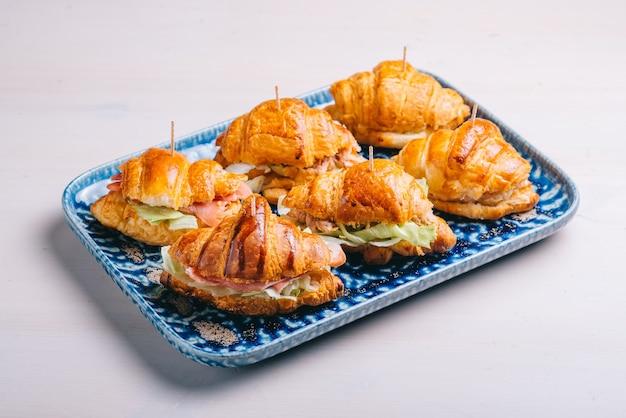 Un ensemble de croissants et sandwichs avec diverses garnitures, fromage, jambon de parme et salade