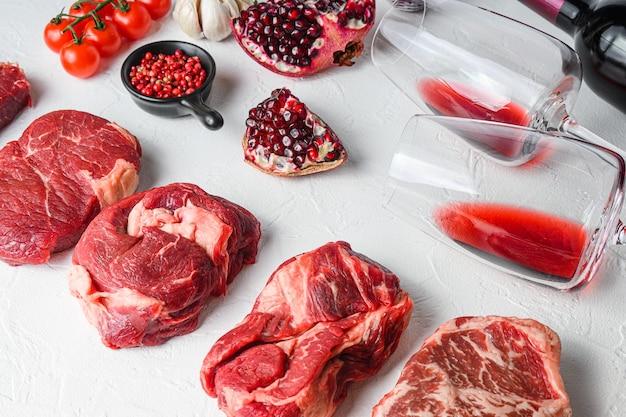 Ensemble cru de coupes de bœuf alternatives chuck eye roll, lame supérieure, rumsteck avec vin rouge en verre et bouteille, herbes et grenade. viande biologique. table texturée blanche. vue de côté.