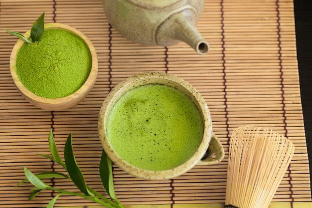 Ensemble de cuillère en bois avec un bol de poudre de matcha et un fouet de feuille de thé vert