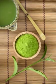 Ensemble de cuillère en bois avec un bol de poudre de matcha et fouet de feuille de thé vert