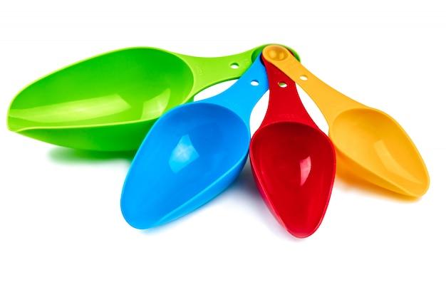 Ensemble de cuillère à mesurer en plastique coloré isolé sur fond blanc avec ombre. cuillère à mesurer en plastique vert, bleu, rouge et orange. jouet enfant
