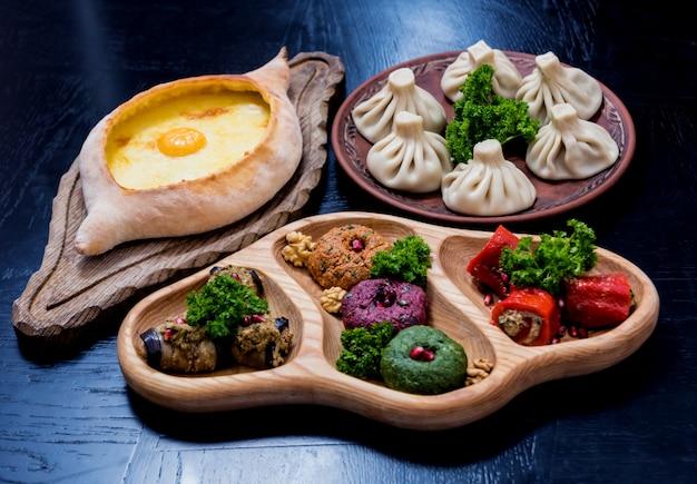 Ensemble de cuisine géorgienne. khachapuri, dolma, satsivi, khinkali, pkhali. restaurant géorgien. contexte