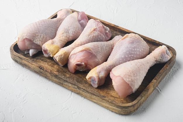 Ensemble de cuisses de poulet bio cru, sur plateau en bois, sur table en pierre blanche