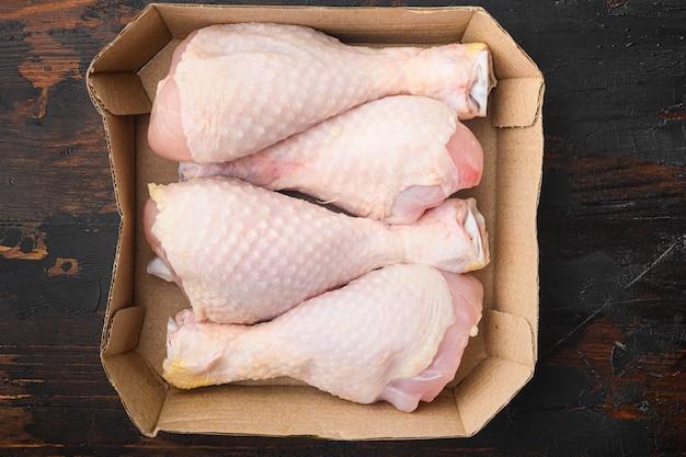 Ensemble de cuisses de poulet frais, en paquet de papier, sur une vieille table en bois foncé, vue de dessus à plat
