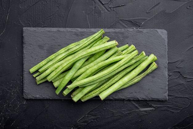 Ensemble de cuisson de haricots verts, sur planche de pierre, sur fond noir, vue de dessus à plat