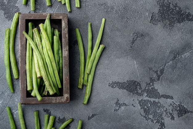 Ensemble de cuisson de haricots verts verts, dans une boîte en bois, sur fond de pierre grise, vue de dessus à plat, avec espace de copie pour le texte