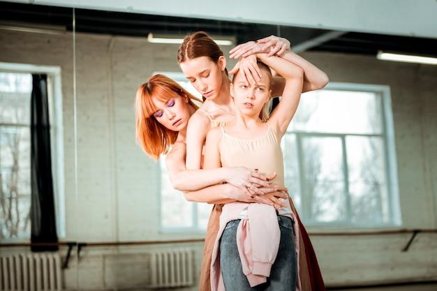 Ensemble dans le studio. jeune professeur de danse aux cheveux roux portant un haut orange et ses élèves apprennent de nouveaux mouvements