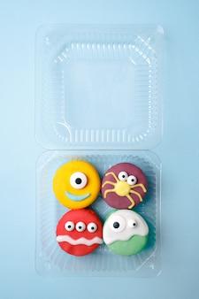 Ensemble délicieux drôle de macarons de monstre pour halloween dans une boîte en plastique sur la surface bleue.