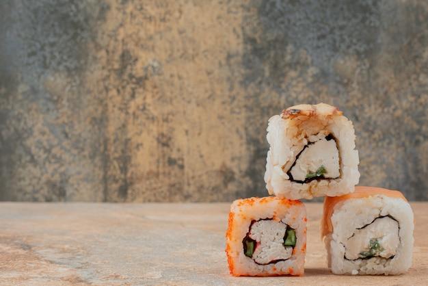 Ensemble de délicieux rouleaux de sushi sur une surface en marbre