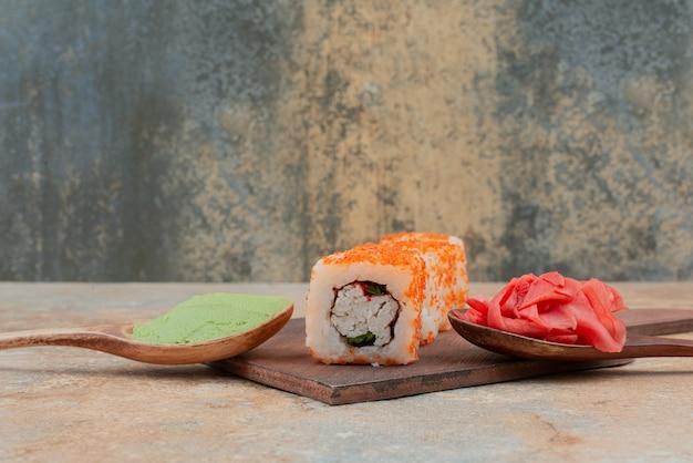 Ensemble de délicieux sushi roll avec cuillère et sauce soja sur marbre