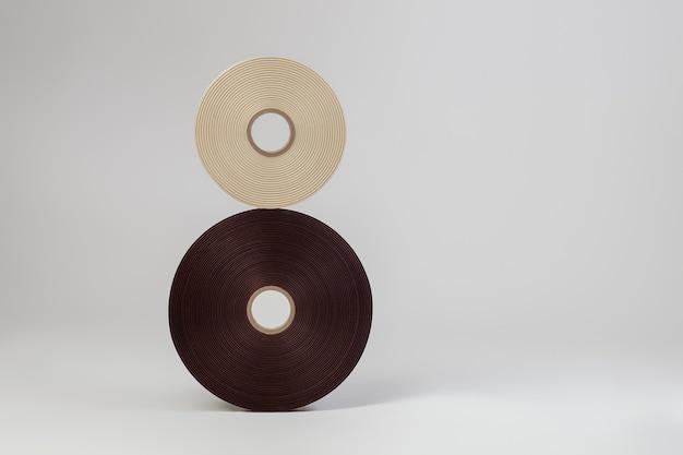 Ensemble de deux bobines de rubans de satin en forme de signe numéro huit ou infini pour étiquettes ou couture en brun blanc isolé