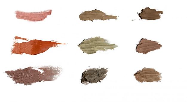 Ensemble de différentes épaisseurs de frottis cosmétiques de couleur sur fond blanc isolé