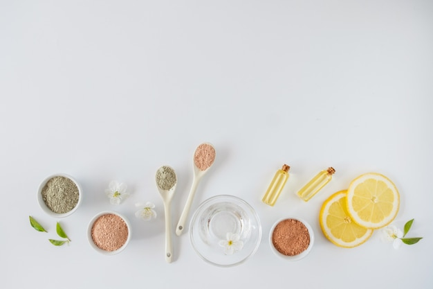 Ensemble de différentes poudres de boue d'argile cosmétique sur une surface blanche. ingrédients pour masque ou gommage pour le visage et le corps faits maison et brin frais de cerise en fleurs. concept de spa et de soins corporels.