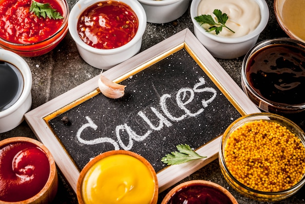 Ensemble de différentes sauces ketchup, mayonnaise, barbecue, soja, teriyaki, moutarde, grain hills, pesto, adzhika, chutney, tkemali, sauce à la grenade sur pierre noire. vue de dessus