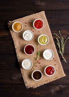 Ensemble de différentes sauces en portions sur un fond rustique en bois foncé. discret.