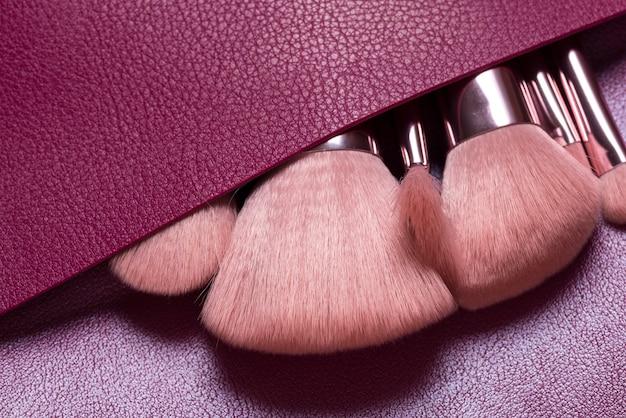 Ensemble de différents cosmétiques brossés dans un sac en cuir
