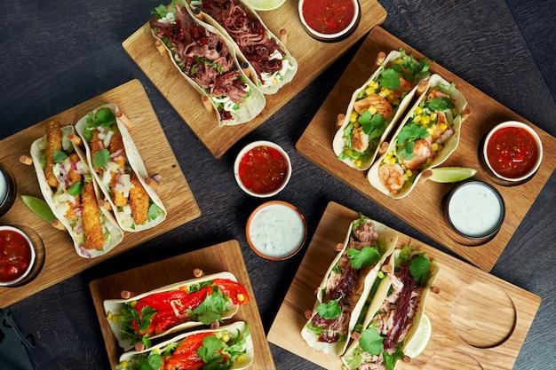 Ensemble de différents tacos avec différentes garnitures - avec poulet, tomates, fruits de mer. image du menu