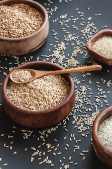 Ensemble de différents types de riz et de céréales dans des bols en bois