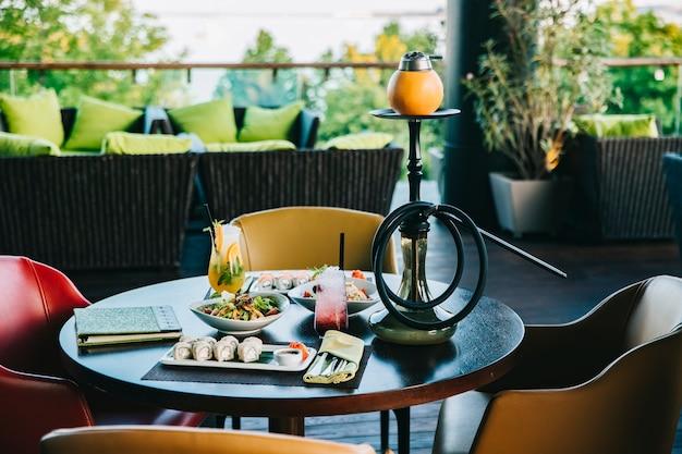 Ensemble de dîner sushi rouleaux salades cocktails narguilé vue latérale