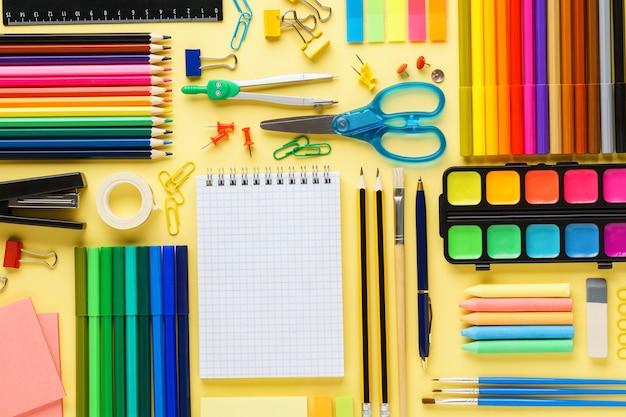Ensemble de divers articles de papeterie et fournitures scolaires colorés sur fond jaune.