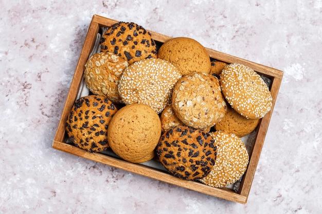 Ensemble de divers biscuits de style américain dans un plateau en bois sur fond de béton clair. sablés aux graines de sésame, beurre d'arachide, flocons d'avoine et biscuits aux pépites de chocolat.