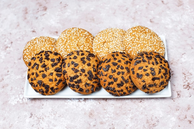 Ensemble de divers cookies de style américain sur un fond de béton clair. sablés aux confettis, graines de sésame, beurre d'arachide, biscuits à l'avoine et aux pépites de chocolat.