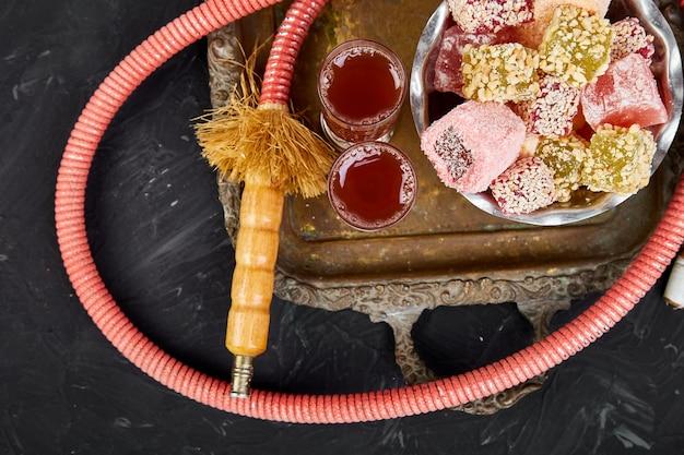 Ensemble de divers délices turcs dans un bol sur un plateau en métal près du tube de narguilé