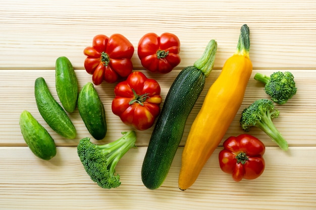 Ensemble de divers légumes d'été sur un fond en bois clair, vue de dessus.