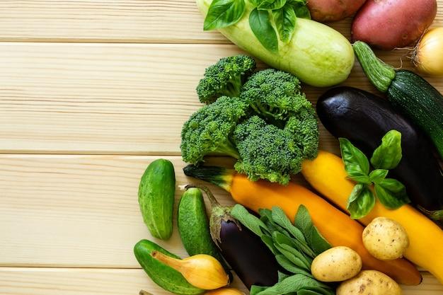Ensemble de divers légumes et herbes sur un fond en bois clair