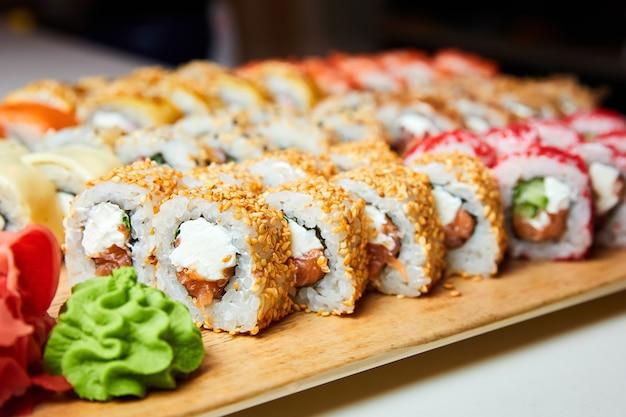 Ensemble de divers rouleaux de sushi sur une planche