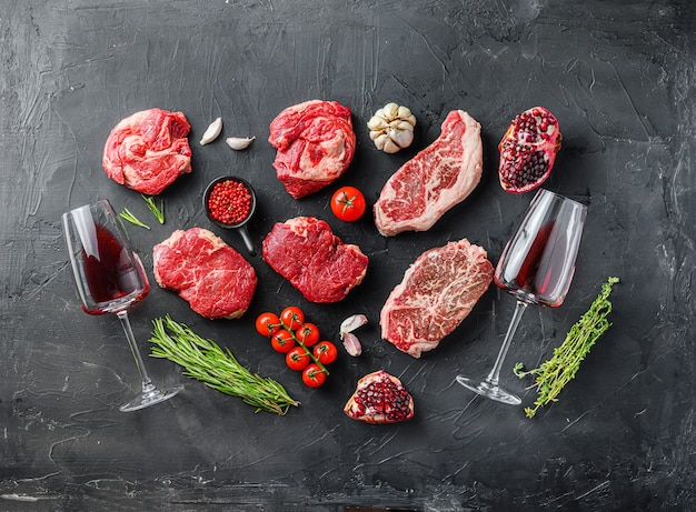 Ensemble de divers steaks crus classiques et alternatifs avec des verres de vin rouge sur fond noir vue de dessus. grande taille.