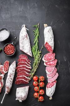 Ensemble de diverses tranches de saucisses de salami séchées à sec espagnoles et de coupes entières sur fond noir, vue de dessus avec espace de copie.