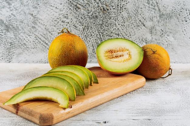 Ensemble de divisé en demi melon sur planche à découper et en tranches de melon sur un fond de pierre blanche. vue de côté.