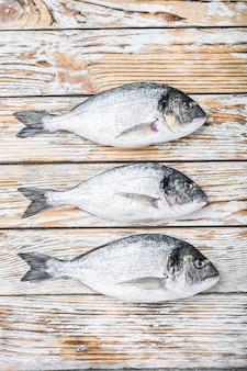 Ensemble de dorada entière crue ou dorade tête de poisson sur table en bois blanc