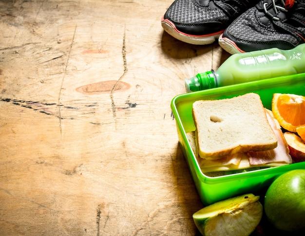 Ensemble du matin. sandwichs au jambon et fromage, un milk-shake et des fruits.
